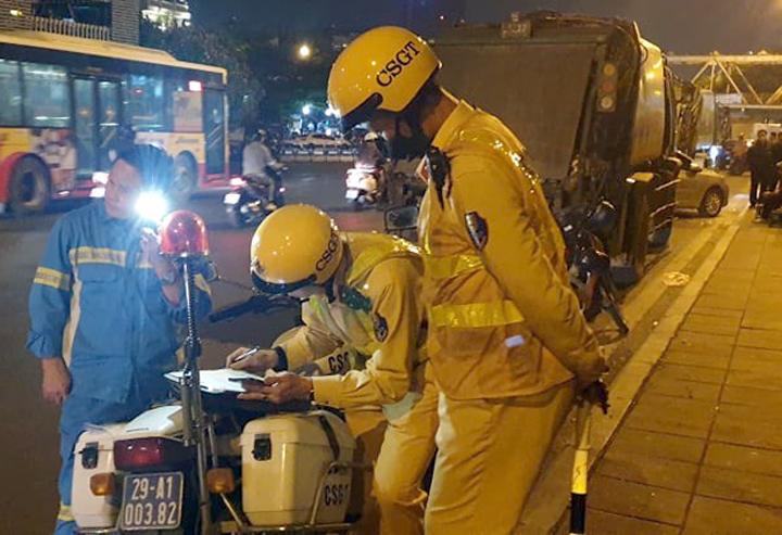 CSGT xử phạt xe chở rác vi phạm về vệ sinh môi trường đêm 25/10. Ảnh: Vân Sơn