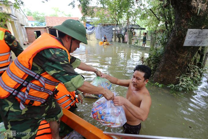 Quân đội dùng canô vượt lũ phát lượng thực cho người dân xã Tam Đàn, huyện Phú Ninh trong sáng 12/10. Ảnh: Đắc Thành