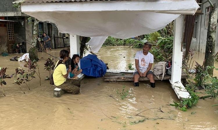 Người dân ngồi cạnh ngôi nhà bị ngập nước do bão Molave ở thị trấn Pola, tỉnh Oriental Mindoro, Philippines hôm 26/10. Ảnh: AFP.