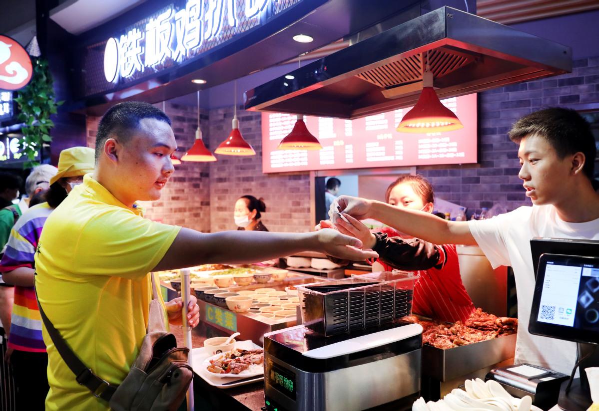 Ang Ziyu (trái) trả tiền mua đồ ăn trong hoạt động đào tạo kỹ năng sống, được tổ chức cho học sinh khiếm thị tại một trung tâm thương mại ở Thượng Hải, ngày 14/8. Ảnh: Xinhua