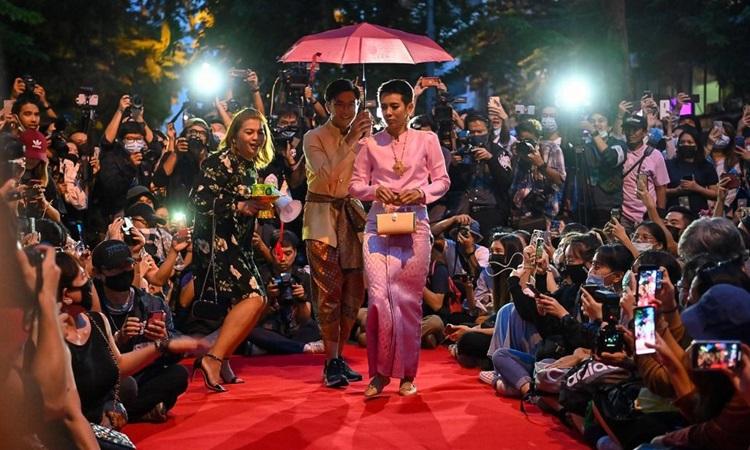Người biểu tình Thái Lan mô phỏng thành viên hoàng tộc trong buổi trình diễn thời trang tại Bangkok hôm nay. Ảnh: Reuters.