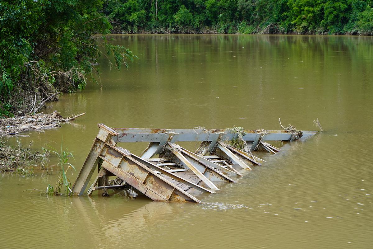 Một phần cây cầu sắt nhô lên mặt nước. Ảnh: Trần Hoá.