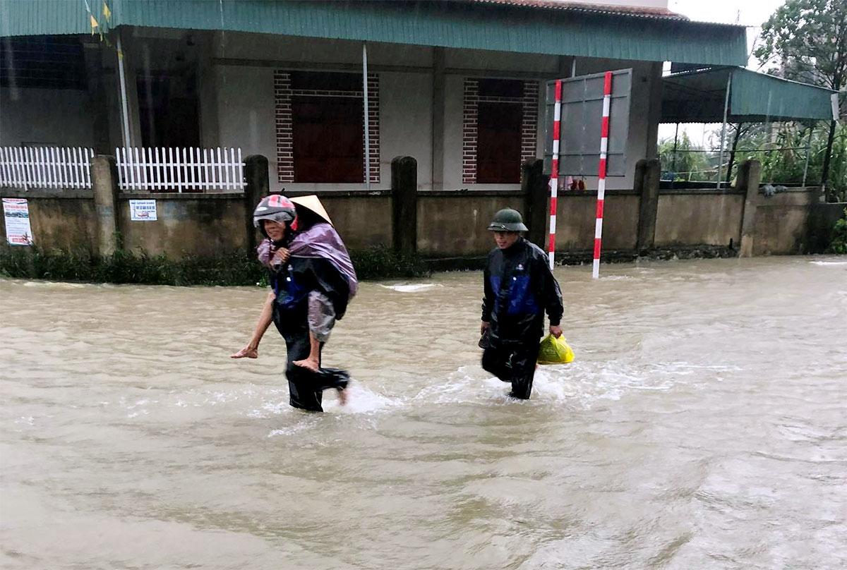 Người dân huyện Can Lộc, Hà Tĩnh cõng nhau đi tránh lũ sáng 30/10. Ảnh: Hùng Lê