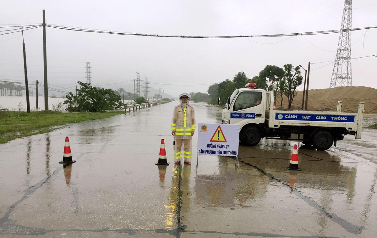 Cảnh sát túc trực ở đầu đoạn quốc lộ bị ngập ở huyện Nghi Xuân, hướng dẫn tài xế đi theo đường tránh. Ảnh: Hùng Lê