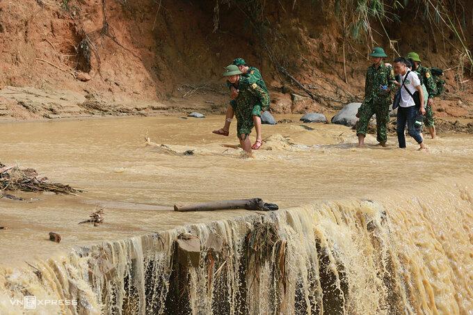 Đường vào hai xã Phước Lộc và Phước Thành bị sạt lỡ, nước chảy xiết băng qua. Ảnh: Quân đội hỗ trợ nhau đi qua đoạn suối tràn để vào xã Phước Công. Ảnh: Võ Thạnh.