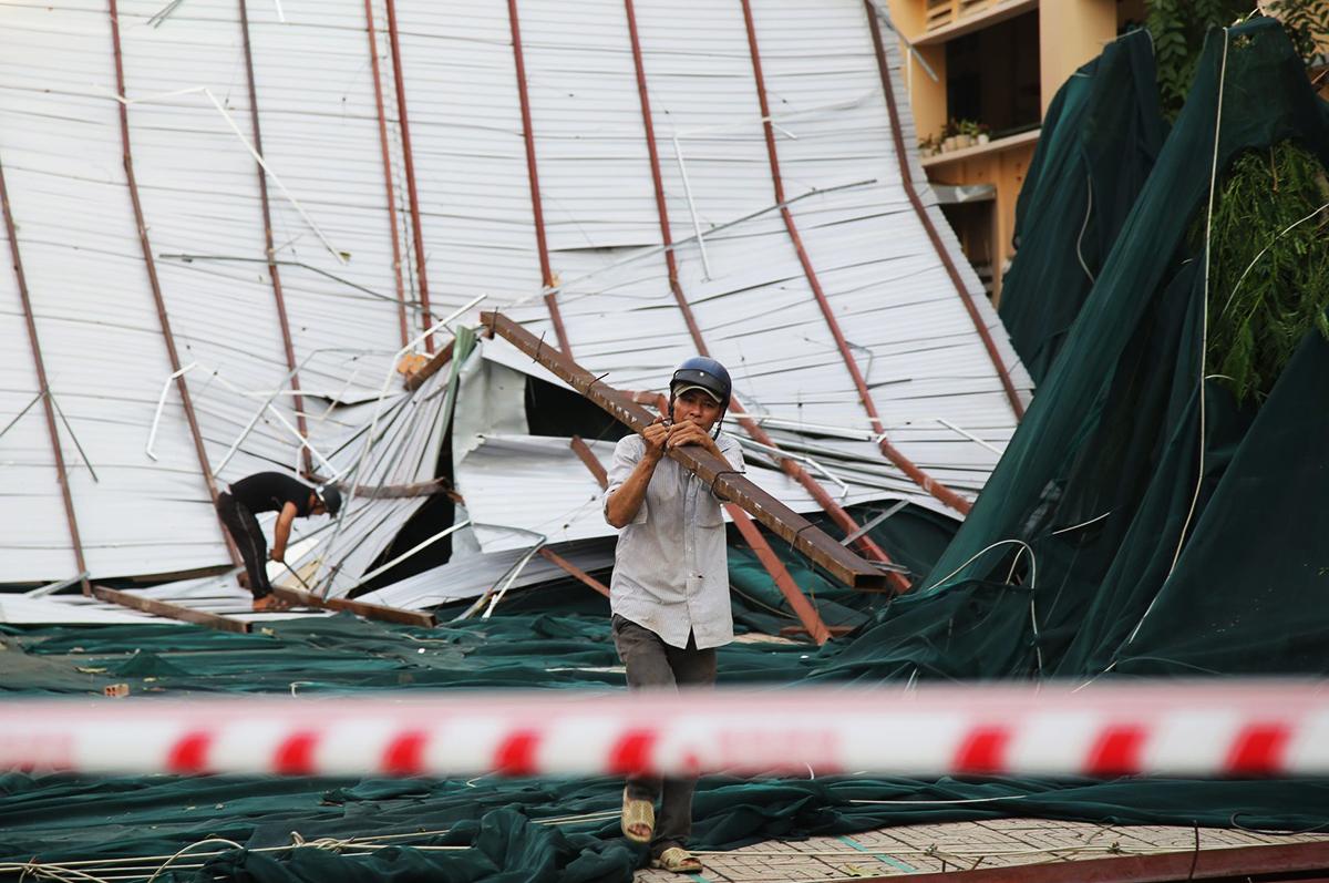 Nhiều người đang tháo dỡ phần mái trường bị lốc cuốn bay xuống sân. Ảnh: Đình Văn.
