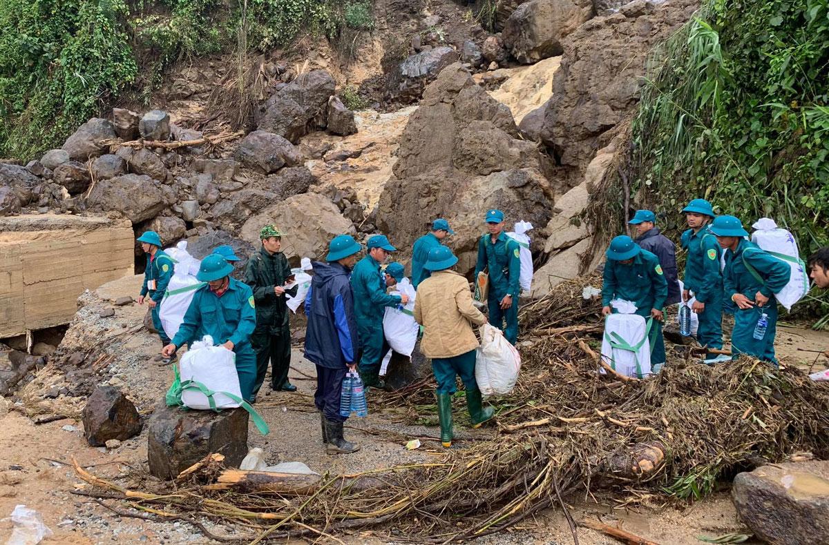 Lực lược chức năng cõng lương thực vượt núi tiếp tế cho người dân xã Phước Thành sáng 1/11. Ảnh: Phạm Trọng.