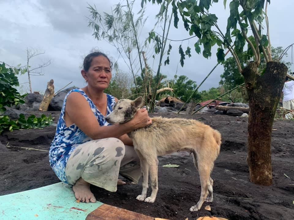 Một phụ nữ an ủi con chó lông đầy bùn đất ở San Francis Co, Guinobatan, tỉnh Albay, sau khi bão Goni khiến 300 ngôi nhà ở đây bị vùi lấp bởi bùn đất từ núi lửa Mayon hôm 1/11. Ảnh: Reuters