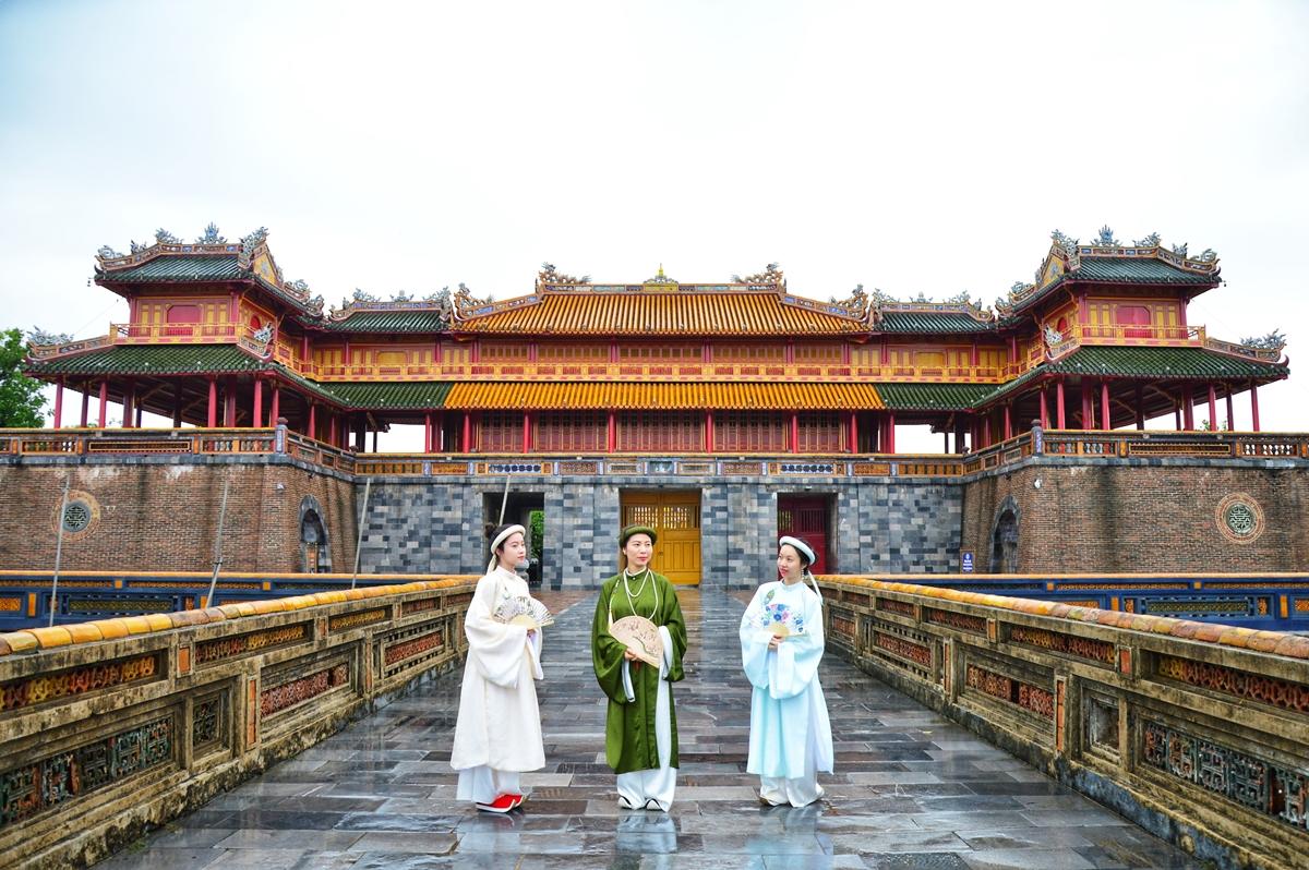 Nhiều du khách thuê áo dài khăn đóng, ngũ thân chụp ảnh trước Hoàng thành. Ảnh: Trân Ơi.