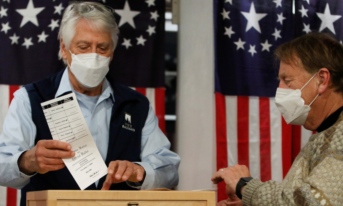 Les Otten (trái) bỏ phiếu tại điểm bầu cử ở Dixville Notch rạng sáng 3/11. Ảnh: Reuters.