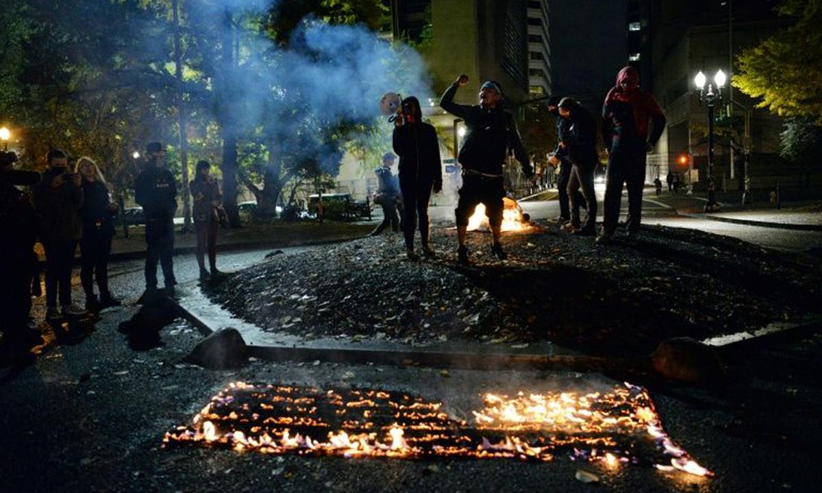 Một lá cờ Mỹ bị đốt bên ngoài trụ sở tòa án liên bang ở Portland, bang Oregon trong đêm bầu cử. Ảnh: AFP.