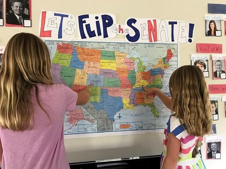 Hai con gái của Richardson sử dụng bản đồ và ảnh của ứng viên để tìm hiểu cách hoạt động của chính phủ Mỹ ở Berkeley, California, hôm 27/8. Ảnh: Reuters