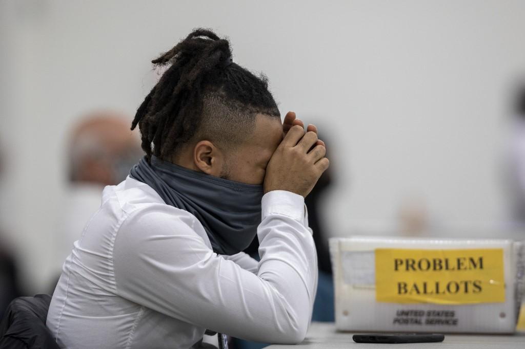 Nhân viên bầu cử ở Detroit sắp xếp phiếu bầu vắng mặt ngày 4/11. Ảnh: AFP.