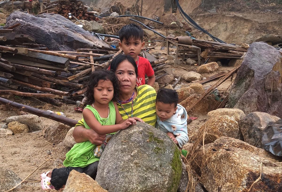 Bà Kíp trông coi  ba đứa trẻ trở về ngôi nhà của mình chỉ còn đá trôi về tấp lên. Ảnh: Đắc Thành.