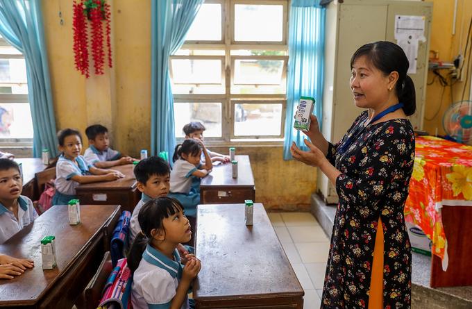 Giáo viên trường Tiểu học Thị trấn Củ Chi (TP HCM) hướng dẫn cho học sinh uống sữa học đường đúng cách vào tháng 6/2020. Ảnh: Quỳnh Trần.