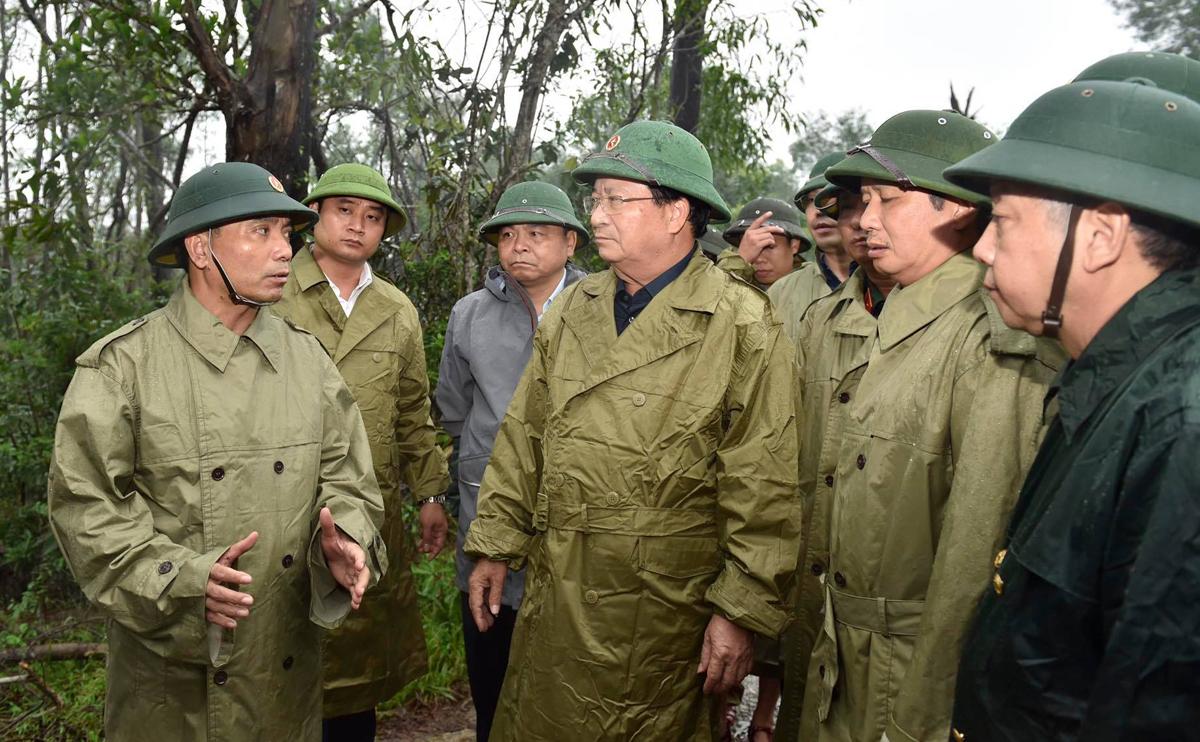 Tư lệnh Quân khu 4 Nguyễn Doãn Anh (bìa trái) báo cáo tình hình với Phó thủ tướng Trịnh Đình Dũng (giữa), chiều 13/10. Ảnh: Đoàn Bắc