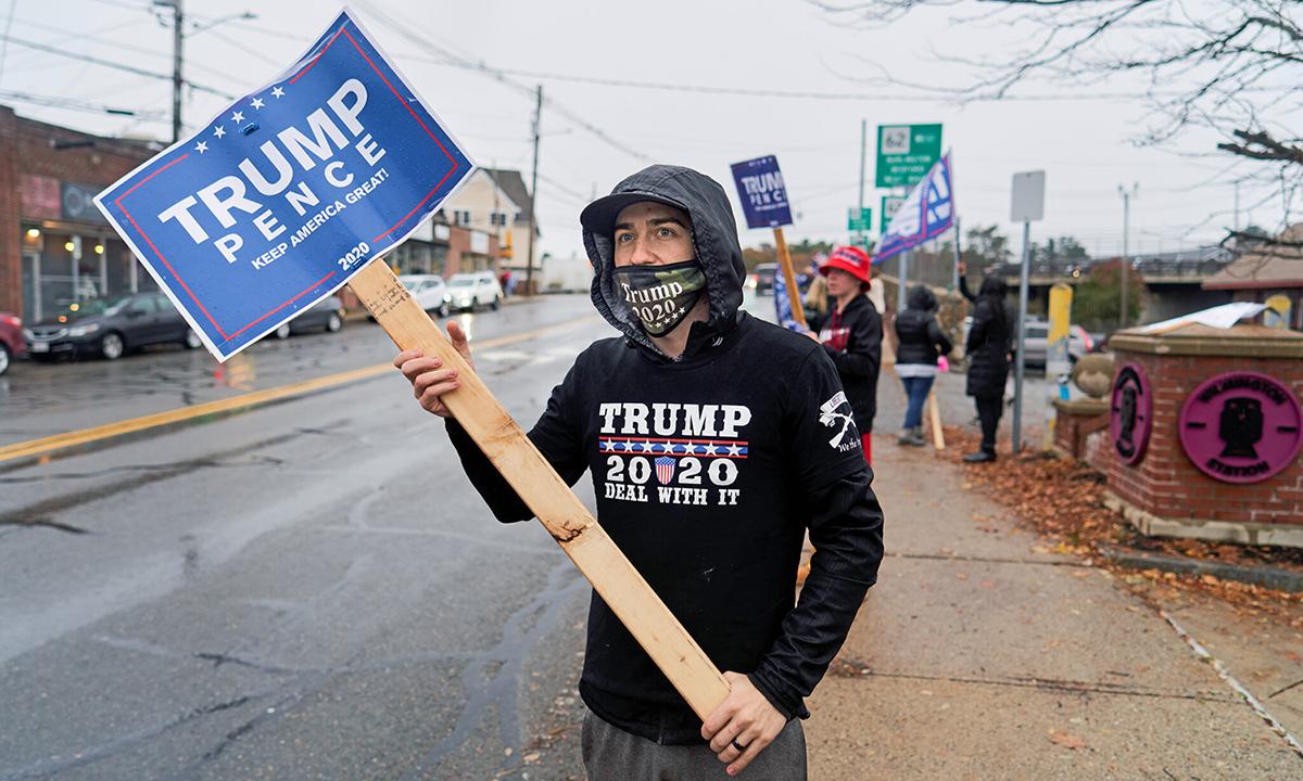 Nick Rocco giơ bảng ủng hộ Tổng thống Trump trên một con phố ở thị trấn Willmington, bang Massachusetts. Ảnh: NYTimes.