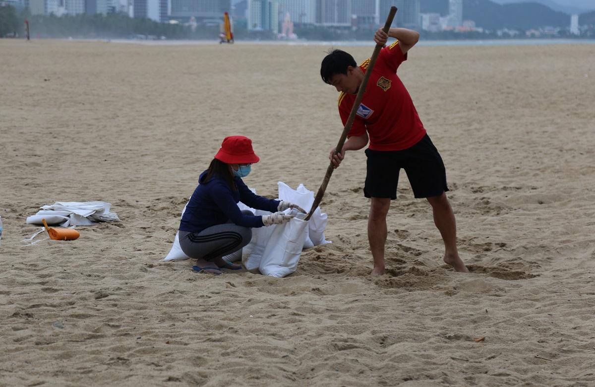 Anh Trí cùng vợ xúc cát bên bờ biển Nha Trang để về giằng chống nhà, chiều 9/11. Ảnh: Xuân Ngọc.