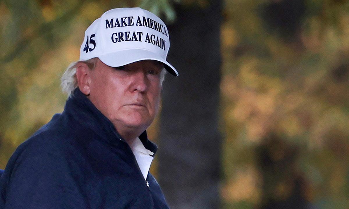 Tổng thống Trump (đội mũ trắng) trở về Nhà Trắng từ sân golf ở Sterling, Virginia hôm 7/11. Ảnh: Reuters.