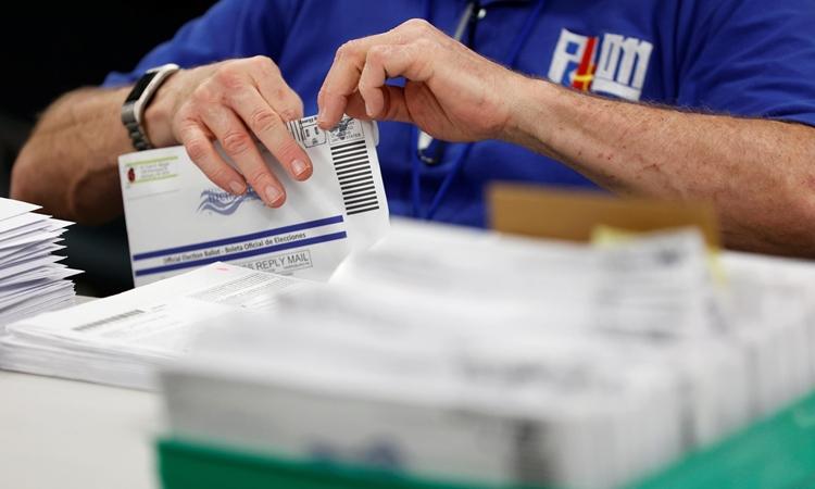 Nhân viên kiểm phiếu qua thư ở hạt Lehigh, bang Pennsylvania, Mỹ, hôm 4/11. Ảnh: Reuters.