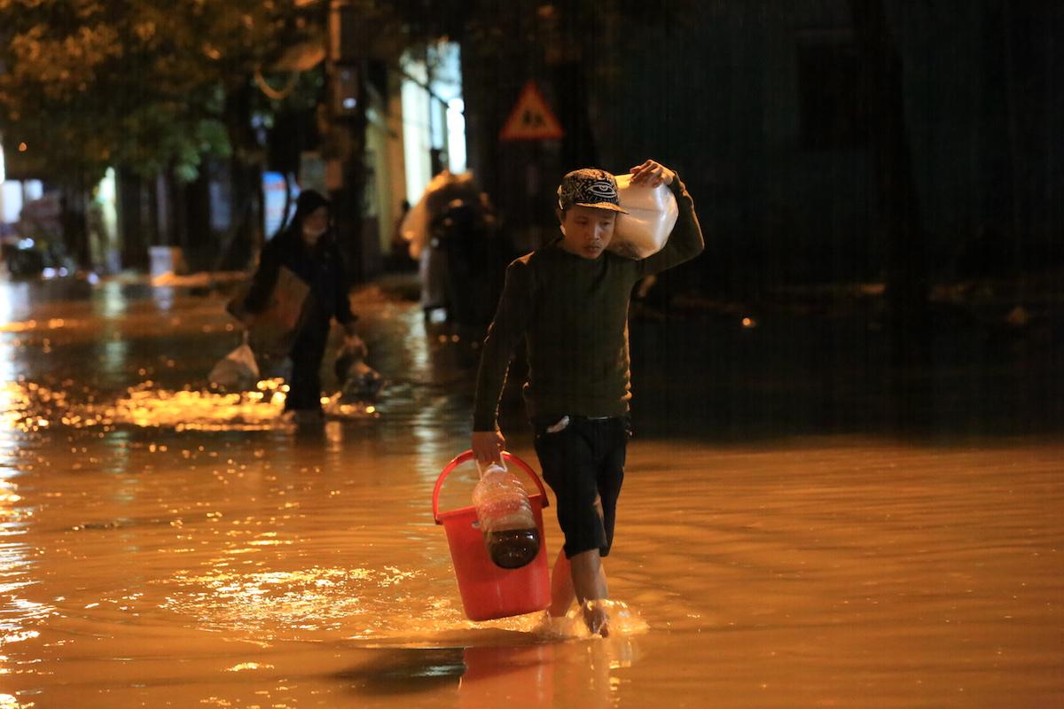 Người dân lội nước lũ trên đường Nguyễn Chí Thanh, TP Huế, tối 11/11. Ảnh: Võ Thạnh