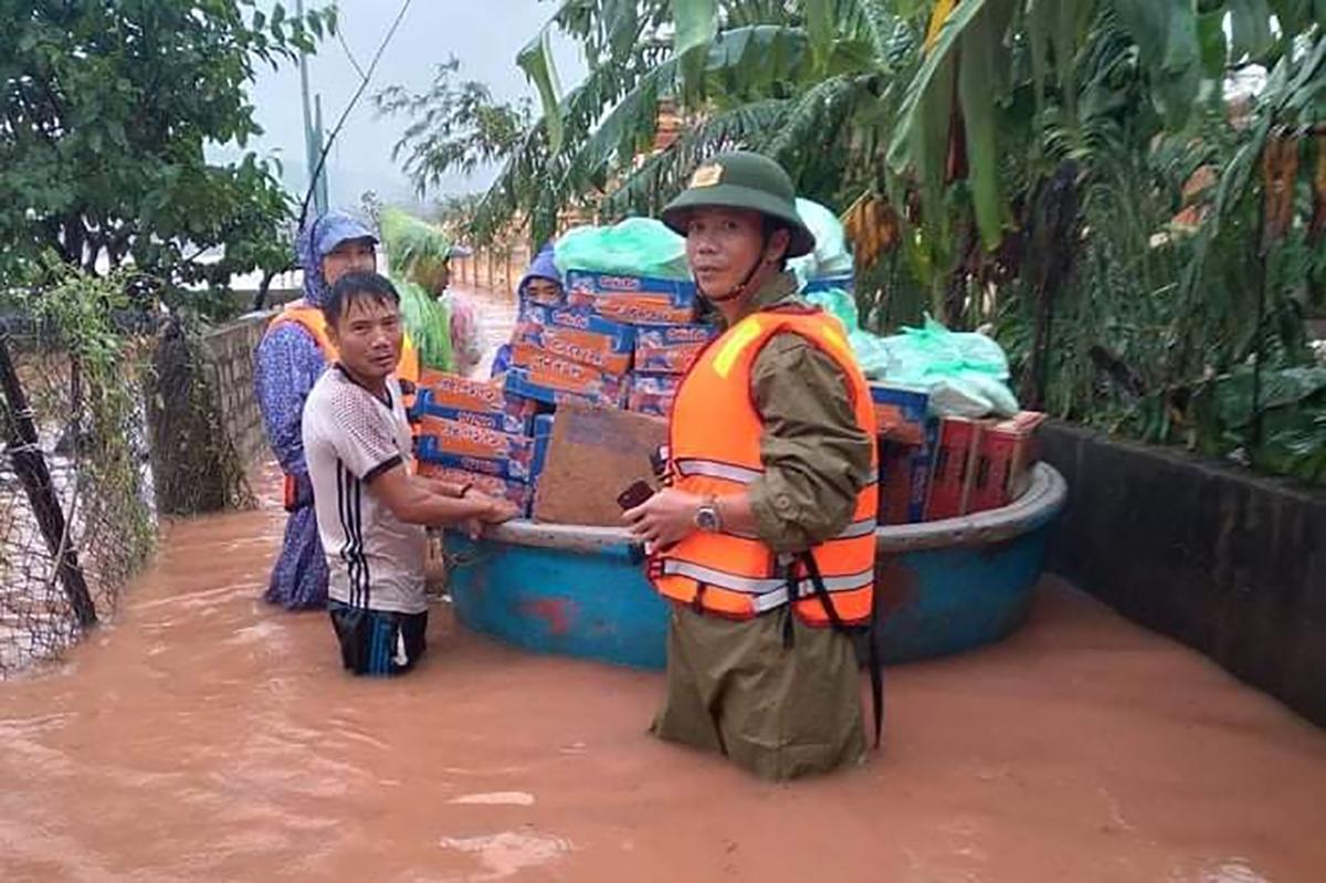 Ông Miên (phải) trong lúc cấp phát lương thực cho người dân thời điểm lũ lụt tháng 10/2020. Ảnh: Quang Hà