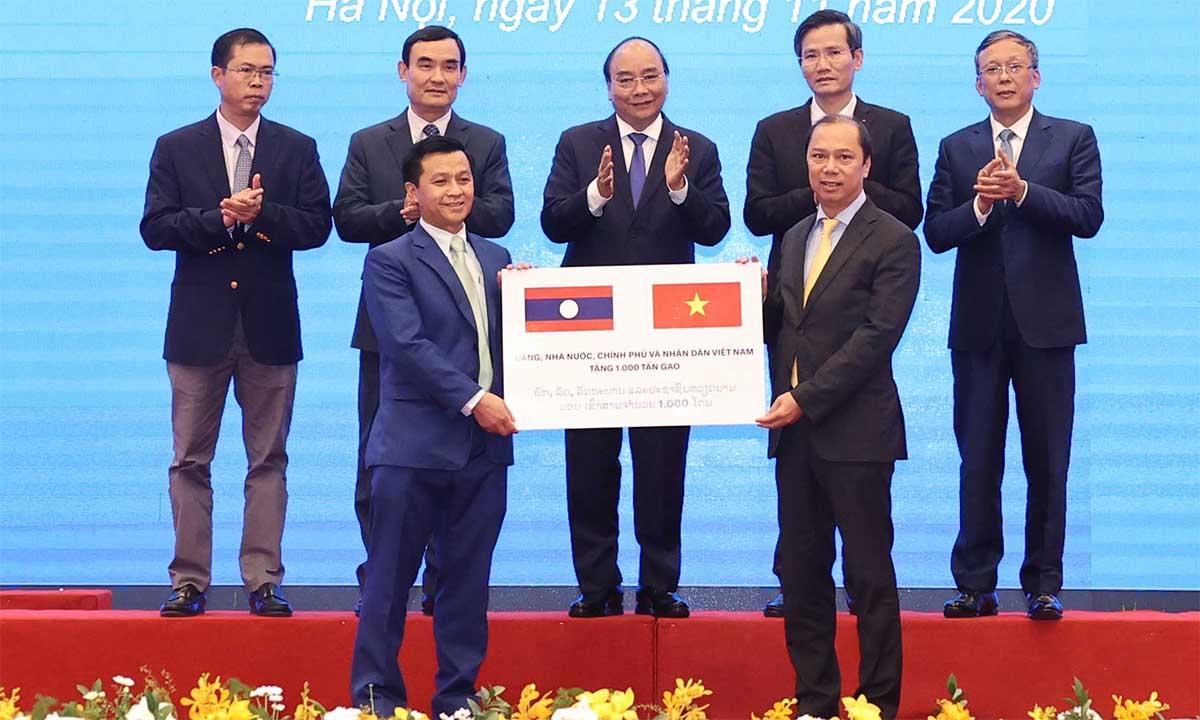 Thứ trưởng Ngoại giao Nguyễn Quốc Dũng (phía trước, bên trái) trao tượng trưng 1.000 tấn gạo cho Phó đại sứ Lào Chanthaphone Khammanichanh (phía trước, bên phải), ngày 13/11. Ảnh: Bộ Ngoại giao.