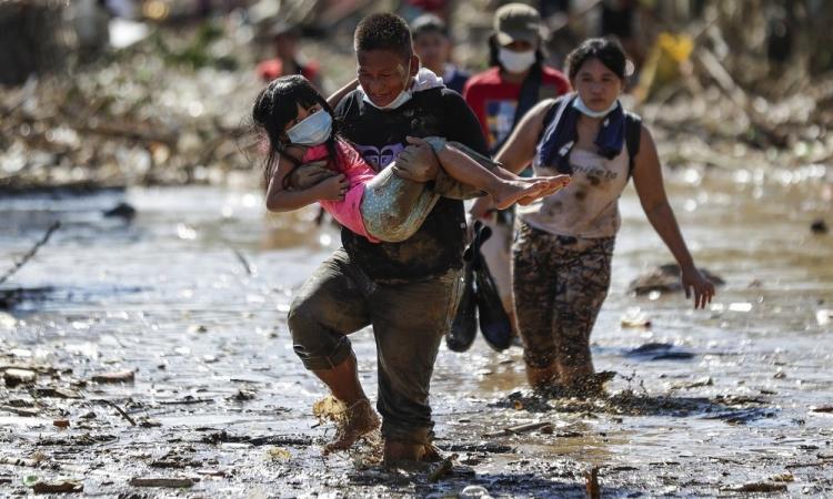 Người dân lội bùn đất tại tỉnh Rizal, Philippines, hôm 13/11. Ảnh: AP.