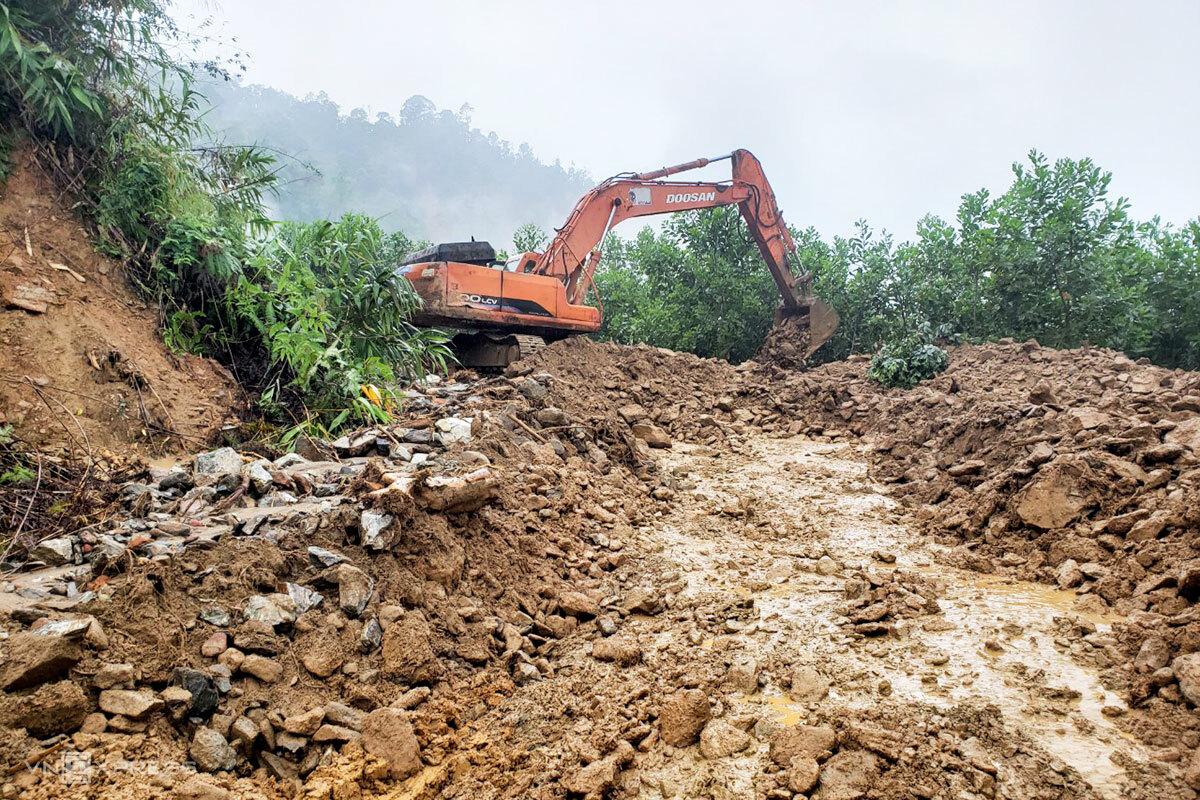 Xe múc đào bới đất sạt lở xuống đường ĐH1, từ xã Phước Kim đến xã Phước Thành, huyện Phước Sơn. Ảnh: Đắc Thành.