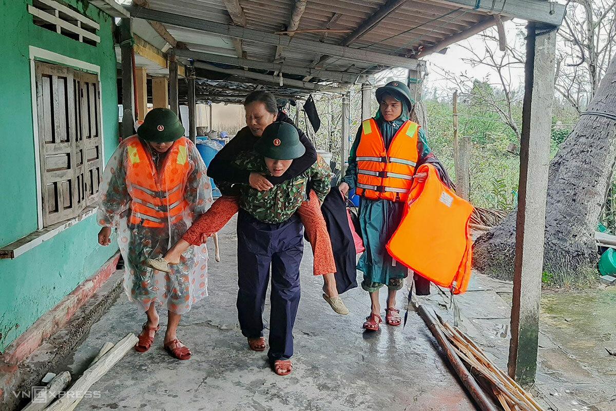 Bộ đội ở Quảng Nam hỗ trợ một người dân bị đau chân sơ tán đến nơi an toàn. Ảnh: Đắc Thành.