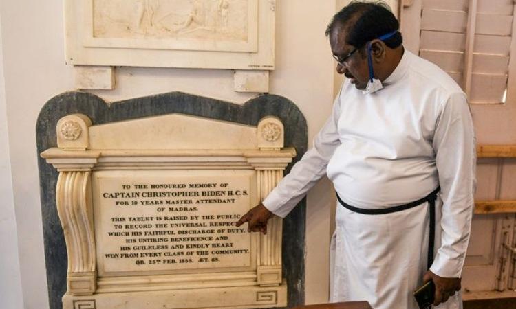 Mục sư chỉ vào tấm bia tưởng niệm Christopher Biden ở nhà thờ St George, thành phố Chennai, Ấn Độ. Ảnh: AFP.