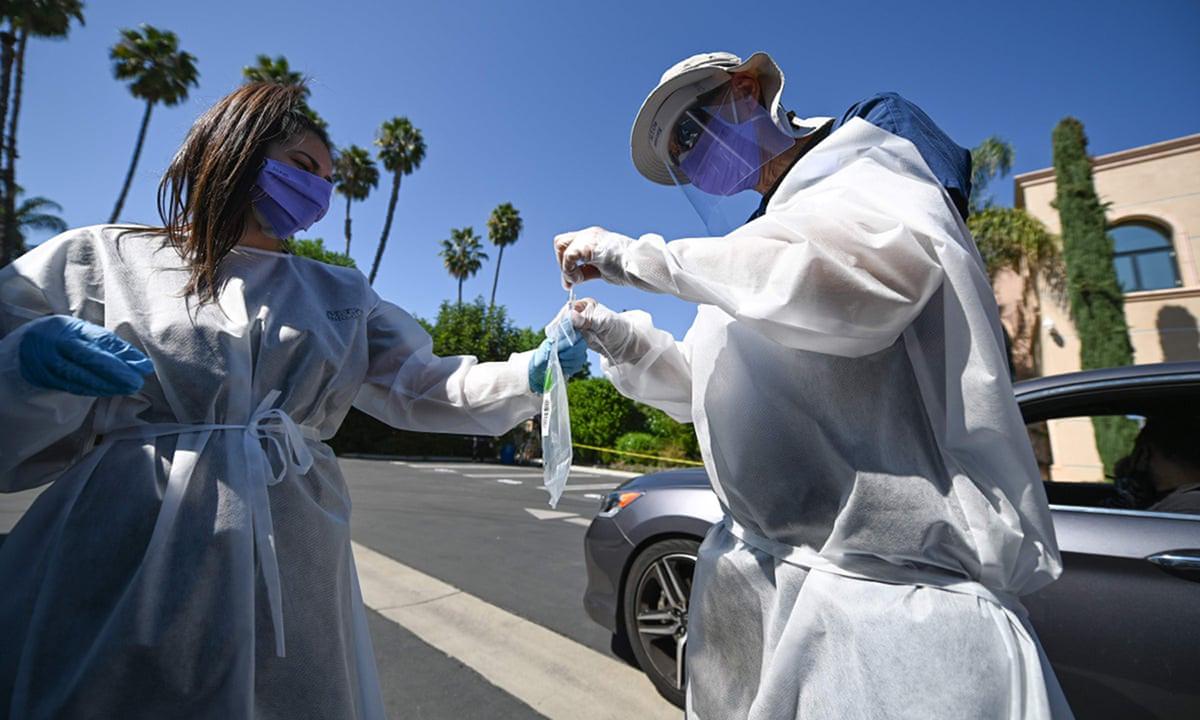 Nhân viên y tế lấy mẫu xét nghiệm Covid-19 cho tài xế tại trung tâm xét nghiệm ở thành phố Los Angeles, bang California. Ảnh: AFP.