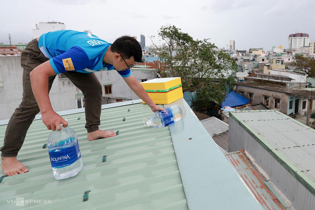 Anh Hiếu (28 tuổi, trú Đà Nẵng) dùng thùng xốp 40 lít chặn góc và gia cố thêm bằng các bình nước đề phòng gió bão làm hư hại mái tôn. Ảnh: Nguyễn Đông.