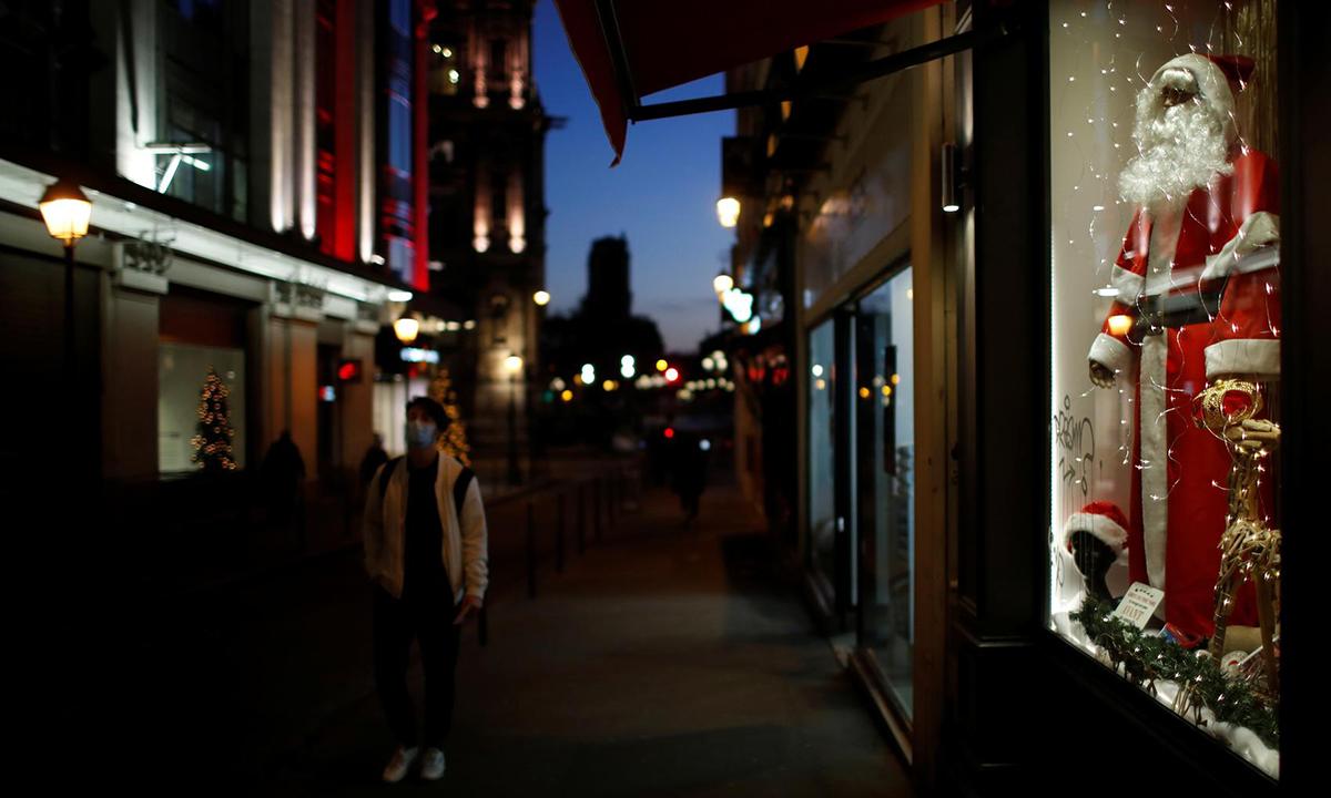 Một người dân đi qua những cửa hàng được trang trí Giáng sinh tại Paris, Pháp, hôm 12/11. Ảnh: Reuters.