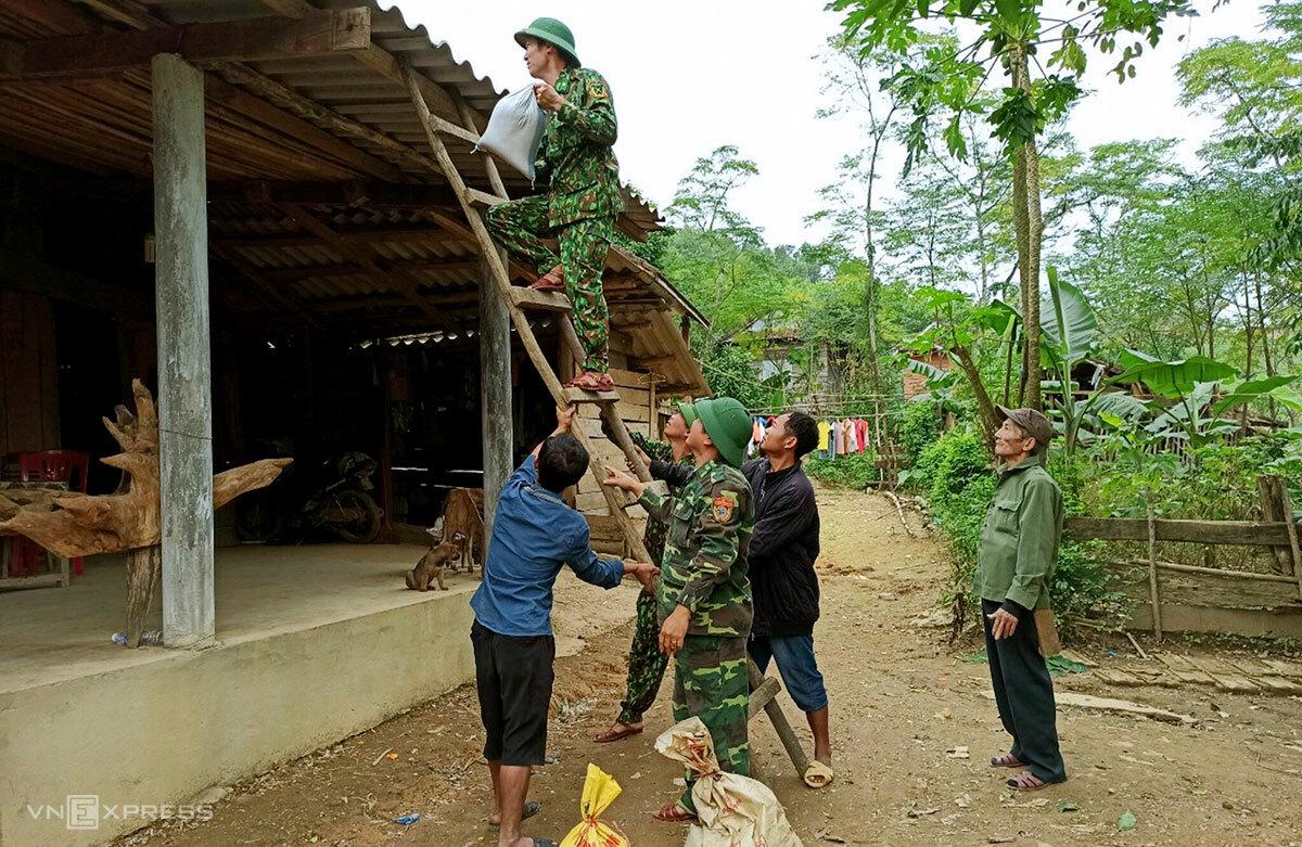 Bộ đội Biên phòng Quảng Bình giúp người giăng để bao cát lên mái nhà chống bão. Ảnh: Hoàng Phương