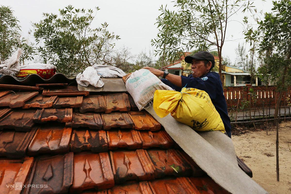 Ông Võ Văn Tuấn đưa bao tải chứa cát lên mái nhà chèn chống sáng 14/11. Ảnh: Đắc Thành.