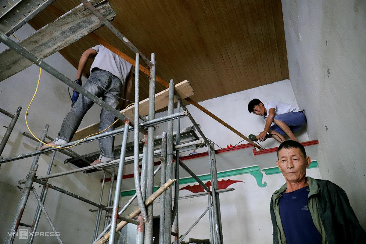Ông Đoàn (mặc áo khoác) đang cùng thợ nề làm lại trần nhà để chống bão. Ảnh: Đức Hùng