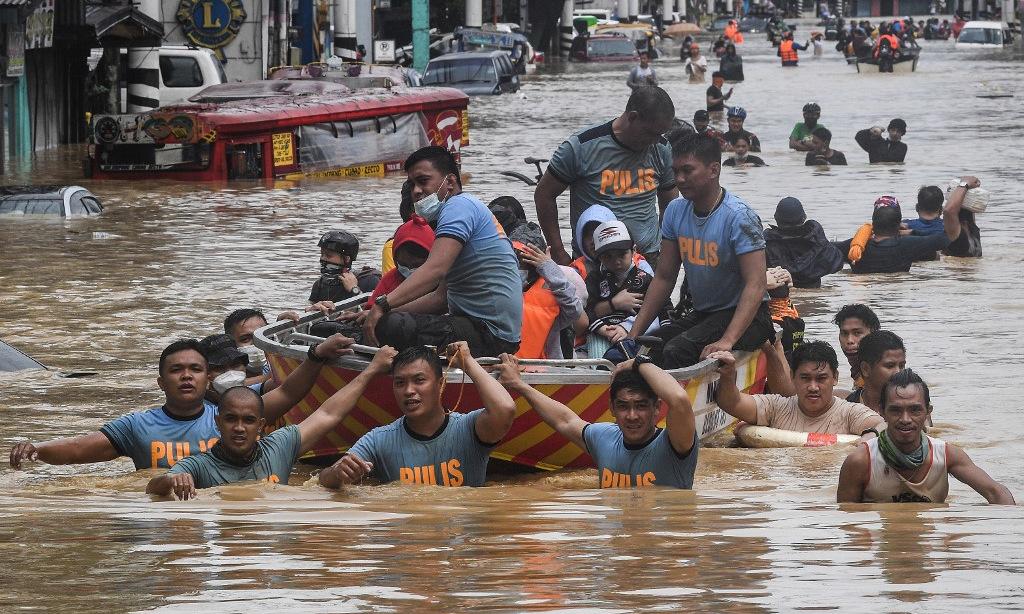 Cảnh sát Philippines hỗ trợ người mắc kẹt ở ngoại ô Manila hôm 13/11. Ảnh: AFP.