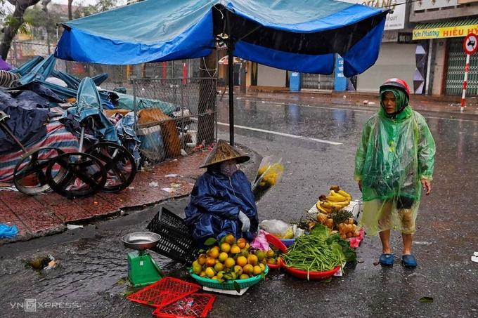 Tiểu thương ở TP Đồng Hới bán hàng dưới trời mưa bão. Ảnh: Giang Huy