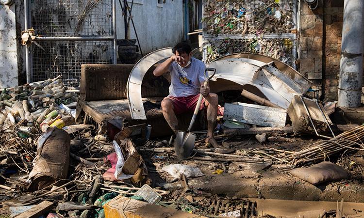 Người đàn ông bật khóc khi dọn dẹp bùn đất bên ngoài ngôi nhà sau bão Vamco  ở thành phố Marikina. Ảnh: Reuters.