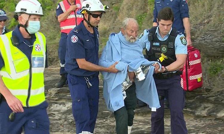 Cụ ông được nhân viên cứu hộ hỗ trợ đi qua mỏm đá trong cuộc giải cứu ở Warriewood, phía bắc Sydney hôm 15/11. Ảnh: TNV.