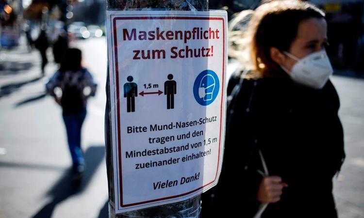 Poster khi thông điệp khuyến cáo người dân đeo khẩu trang và giãn cách xã hội tại Berlin, Đức. Ảnh: AFP.