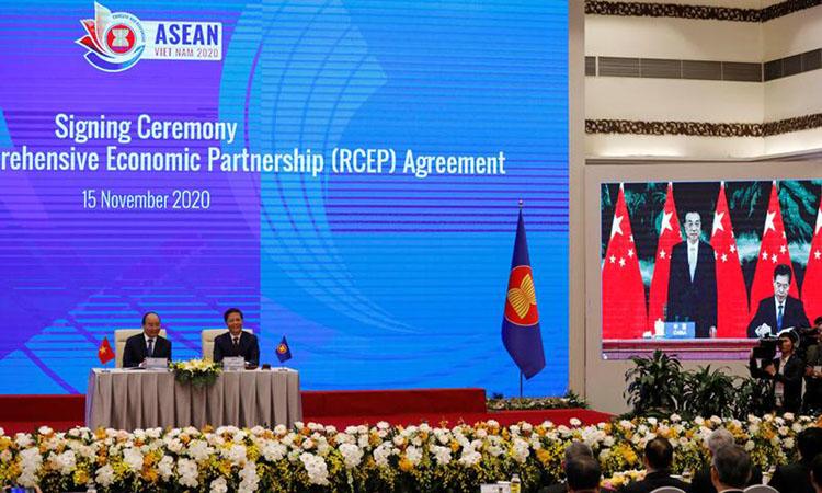 Thủ tướng Nguyễn Xuân Phúc ngồi cạnh Bộ trưởng Bộ Công Thương Trần Tuấn Anh khi màn hình cho thấy Bộ trưởng Bộ Thương mại Trung Quốc Chung Sơn đang ký RCEP cạnh Thủ tướng Lý Khắc Cường hôm 15/11. Ảnh: Reuters.