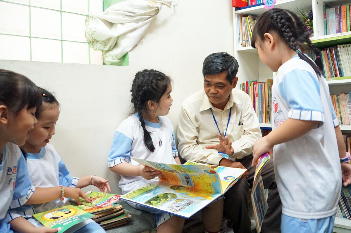 Thầy Nguyễn Văn Hùng và học sinh trường Tiểu học Mê Linh tại thư viện trường trong giờ ra chơi trưa 18/11. Ảnh: Mạnh Tùng.