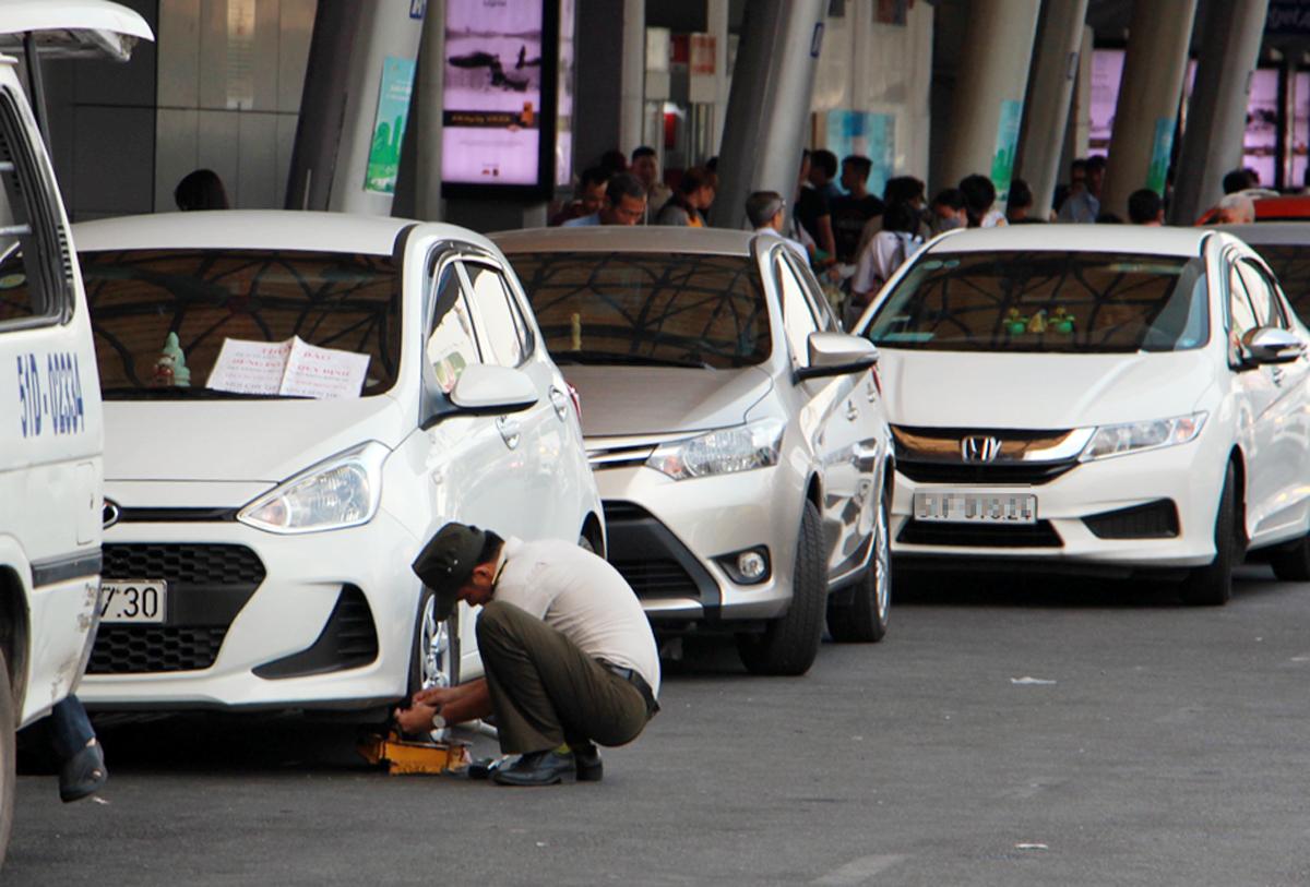 Nhân viên an ninh sân bay Tân Sơn Nhất khoá bánh một ôtô, chờ cẩu đi do đậu quá thời gian trên làn A nhưng tài xế không có mặt, năm 2018. Ảnh:Gia Minh.
