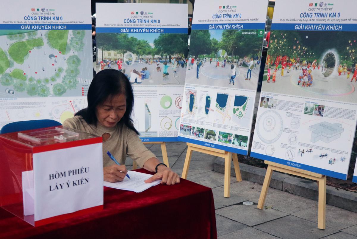 Bà Nguyễn Thị Thanh Hằng, trú tại 22 Hàng Vải, phường Hàng Bộ, quận Hoàn Kiếm đóng góp ý kiến vào các phương án đạt giải cuộc thi thiết kế Km0. Ảnh: Võ Hải.