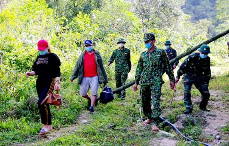 Hạnh (áo đen) và Ánh (áo phông đỏ) bị Bộ đội Biên phòng dẫn về đồn khai báo y tế. Ảnh: Đức Hùng