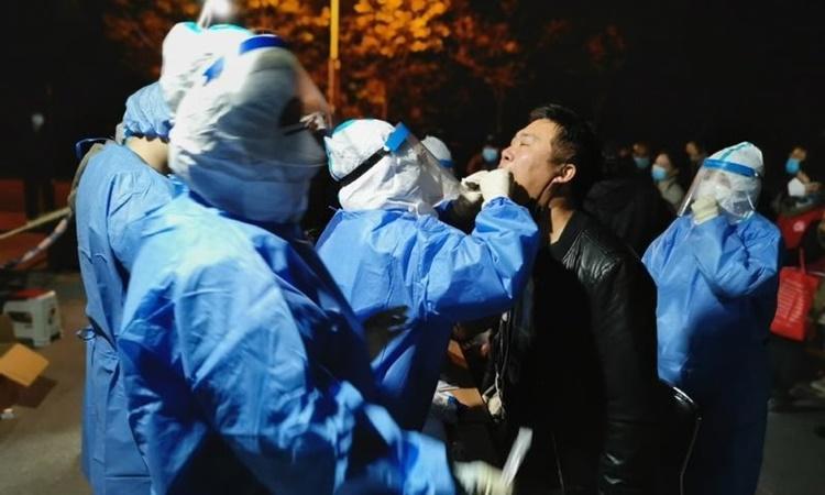 Nhân viên y tế lấy mẫu xét nghiệm nCoV cho người dân ở quận Tân Hải, thành phố Thiên Tân, Trung Quốc, hôm 10/11. Ảnh: Xinhua.