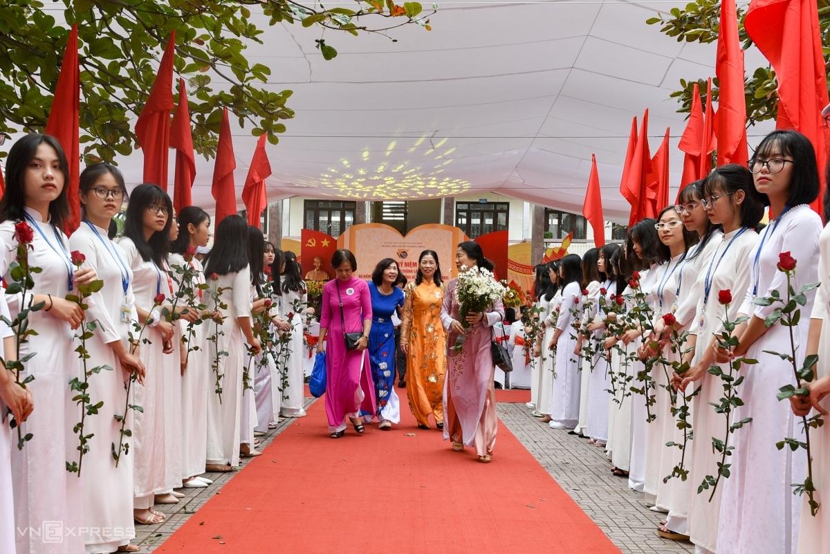 Các nữ sinh trường THPT chuyên Lê Hồng Phong cầm hoa chào mừng cựu học sinh, giáo viên về thăm trường nhân dịp kỷ niệm 100 năm thành lập, sáng 22/11. Ảnh Thanh Huế