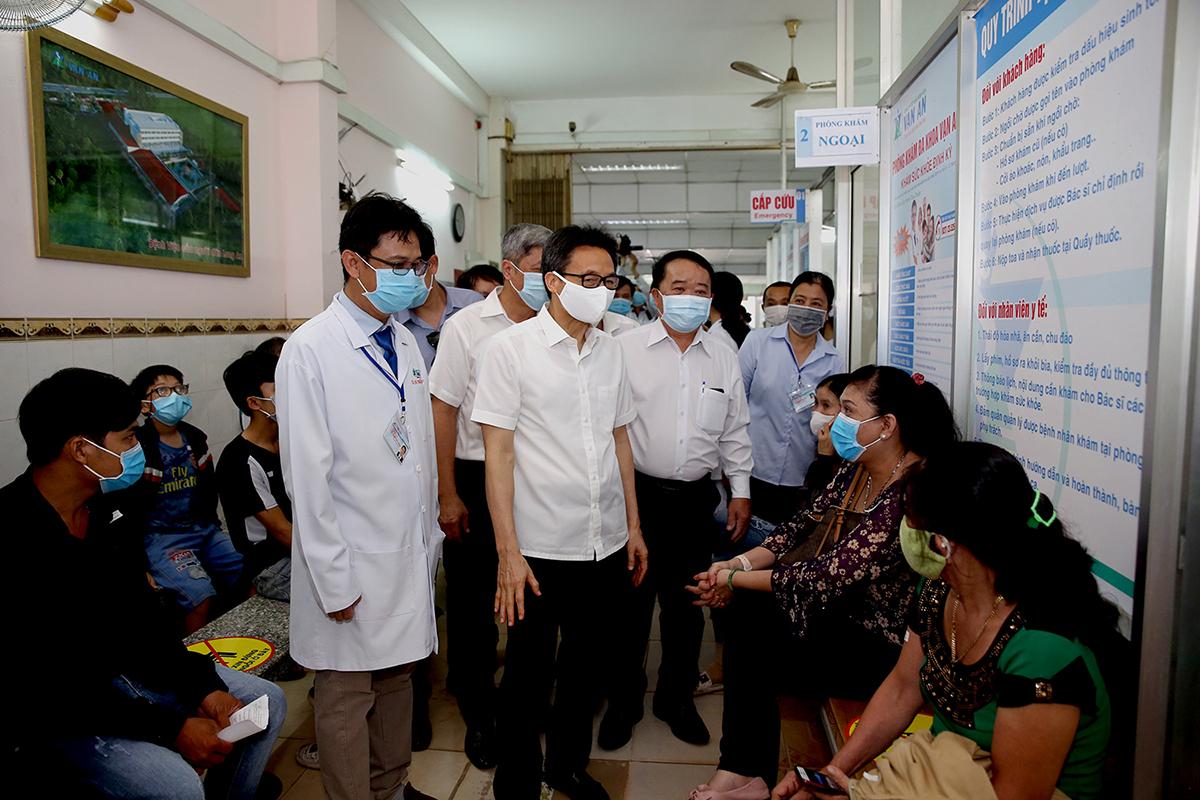 Phó Thủ tướng Vũ Đức Đam nói chuyện với người dân đến khám bệnh tại Phòng khám đa khoa Vạn An, TP Tân An, tỉnh Long An. Ảnh: Đình Nam